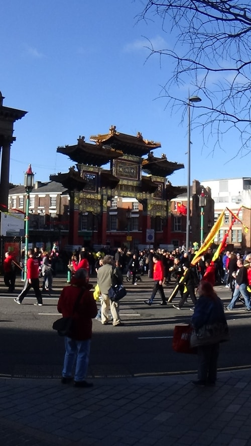 Chinese New Year Liverpool 2016 parade with flags with Chinese Arch in background at entrance to Chinatown 7th February 2016