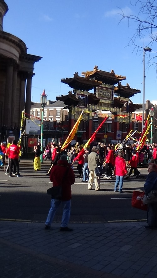 Chinese New Year Liverpool 2016 parade with flags with Chinese Arch in background at entrance to Chinatown 7th February 2016 photo 2