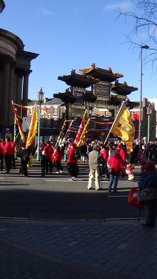Chinese New Year Liverpool 2016 parade with flags with Chinese Arch in background at entrance to Chinatown 7th February 2016 photo 3