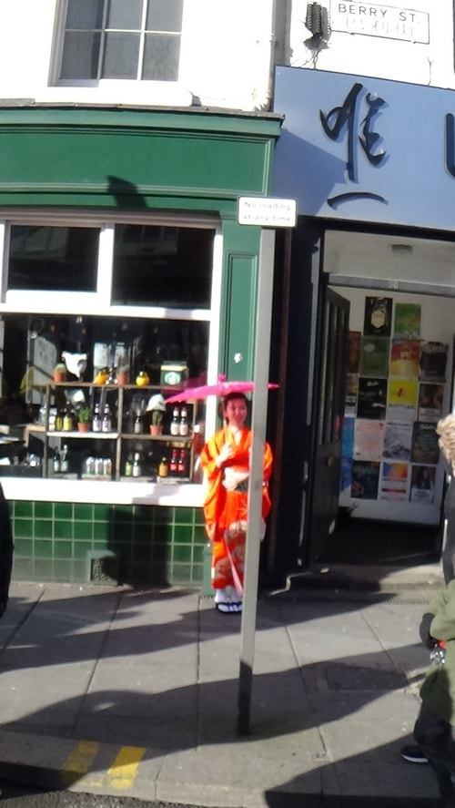 Chinese New Year Liverpool 2016 woman in costume with umbrella outside shop  7th February 2016