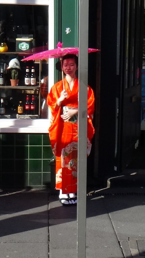 Chinese New Year Liverpool 2016 woman in costume with umbrella outside shop photo 2  7th February 2016